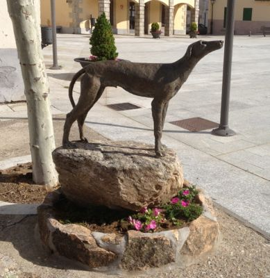 Hound bronze statue in a public square in a Spanish village